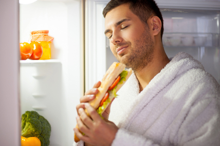 guilty pleasure: The best sandwich ever. Satisfied young man in bathrobe standing near the open fridge and eating sandwich with his eyes closed