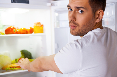 Feeling so hungry. Surprised young man standing near the open fridge and stretching hand to sandwich laying inside photo