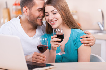 Romantic moments. Beautiful loving couple sitting at the laptop and drinking wine  photo