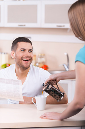 Happy Sunday morning. Woman pouring coffee to the cup while happy young man holding newspaper and smiling  photo