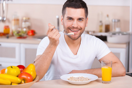 eating utensils: Healthy breakfast. Handsome young man having a healthy breakfast while sitting in the kitchen Stock Photo