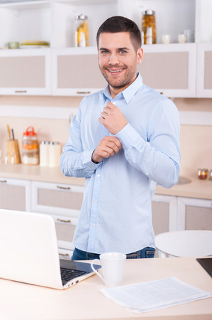 his shirt sleeves: Morning dress up. Happy young man adjusting sleeves on his shirt and looking at camera while standing in the kitchen