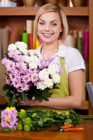 flower bunch: Making a beautiful flower bunch. Beautiful young blond hair woman in apron arranging flowers and looking at camera