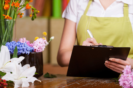 Female florist at work. Cropped image of female florist writing something at note pad while standing at her working place photo