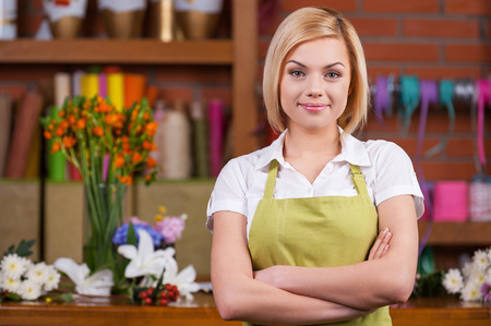 Beautiful florist at working place. Beautiful young female florist keeping arms crossed and looking at camera while standing near her working place  photo