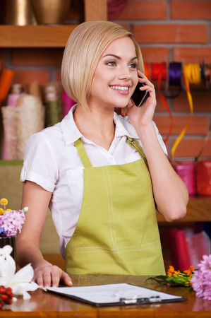 She knows everything about flowers. Beautiful young female florist taking on the phone and smiling while standing at her working place photo
