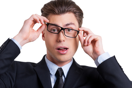 Businessman grimacing. Playful young man in formalwear adjusting his glasses and grimacing while looking at camera and standing isolated on white photo