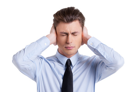 Sick and tired. Frustrated young man in shirt and tie covering ears with hands and keeping eyes closed while standing isolated on white photo