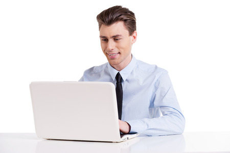 Businessman working on laptop. Handsome young man in shirt and tie sitting at the table and working on laptop while isolated on white