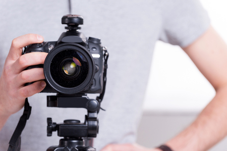 Ready to shoot. Close-up of man holding digital camera while standing in studio with lighting equipment on background  Stock Photo - 27688530