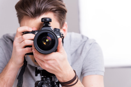 studio: Smile! Young man focusing at you with digital camera while standing in studio with lighting equipment on background  Stock Photo