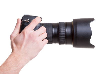 handcarves: Digital camera. Side view of man holding digital camera while isolated on white