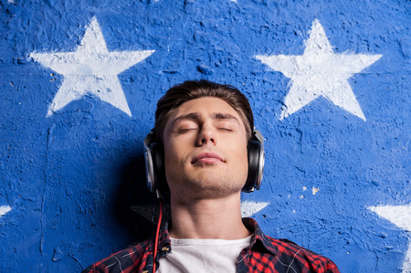 Enjoying music. Low angle view of young man in headphones keeping eyes closed while standing against background photo