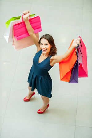 I love shopping! Top view of beautiful young woman holding shopping bags and smiling at camera