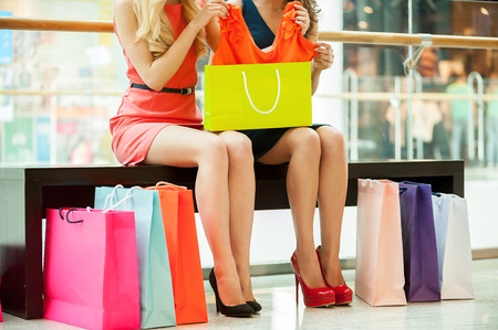 Women shopping. Cropped image of two young women sitting in shopping mall with bags Stock Photo