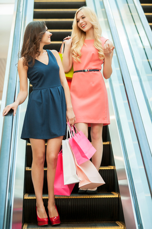 spending full: Shopping together is fun. Two girls standing on escalator and carrying shopping bags