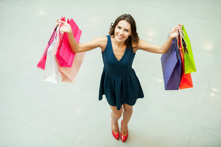 Look what I get! Top view of beautiful young woman holding shopping bags and smiling at camera Stok Fotoğraf