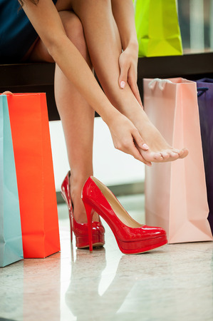 Tired of day shopping. Cropped image of young woman resting and massaging her toes with shopping bags near her photo