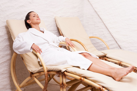 Woman in salt room. Beautiful young woman in bathrobe relaxing in salt room