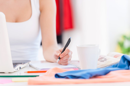working place: Working in design studio. Cropped image of woman working at her working place with colorful cloth laying on the table Stock Photo