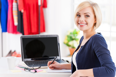 Confident and creative. Beautiful young woman looking over shoulder and smiling while sitting at her working place photo