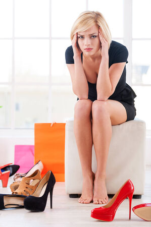 shoe store: Woman in shoe store. Depressed young woman holding head in hands and looking at camera while sitting at the shoe store