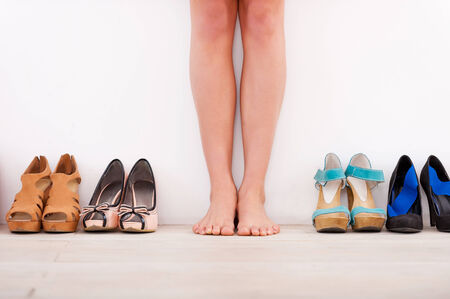 Making her choice. Cropped image of young woman standing against the wall while different shoes laying in a row near her photo