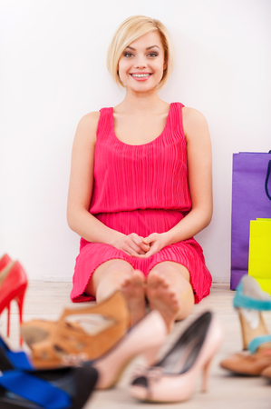 Shopaholic woman. Beautiful young woman in pink dress sitting against the wall while different shoes laying on foreground holding  photo