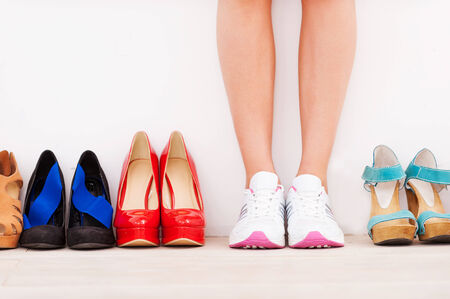 I made my choice! Cropped image of woman in sports shoes standing against the wall while high hilled shoes laying in a row near her photo
