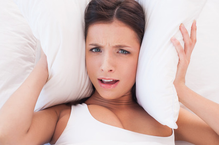 cant: Too much noise. Beautiful young woman covering ears by pillow because of noise