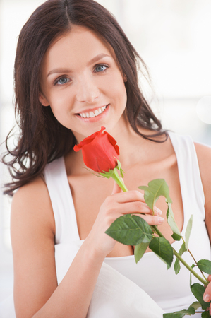 Beauty with flower. Attractive young woman holding a red rose and smiling at camera  photo