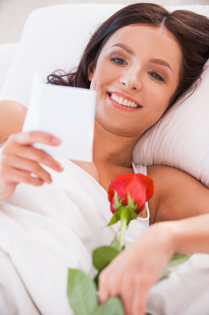 Message from boyfriend. Close up image  of beautiful young woman lying in bed with red rose and reading letter  photo