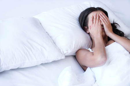 ojos llorando: Las mujeres deprimidas en la cama. Vista superior de la mujer triste joven tumbado en la cama y ocultando su rostro en las manos