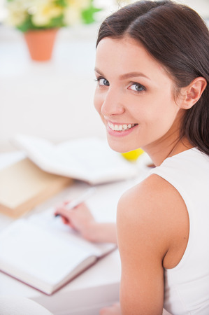 over the shoulder view: Making notes. Rear view of young beautiful woman writing something in her note pad and smiling at camera Stock Photo