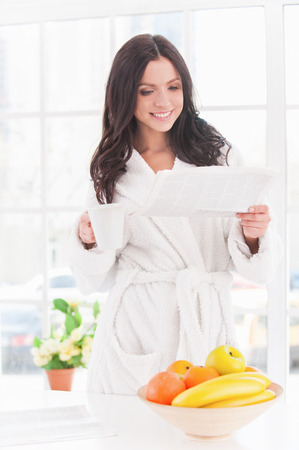 Reading morning news. Beautiful young smiling woman in bathrobe reading newspaper with cup of coffee photo