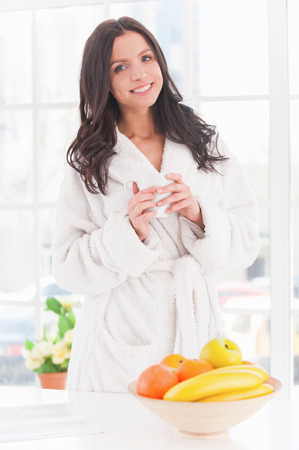 Morning coffee. Beautiful young smiling woman in bathrobe holding cup of coffee and smiling on camera photo