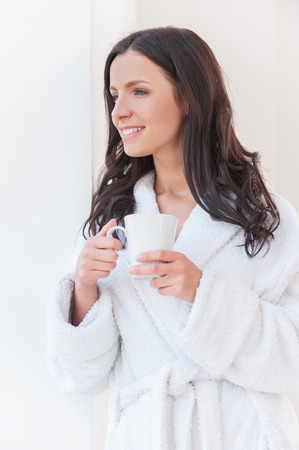 Drinking coffee at the morning. Beautiful young woman in bathrobe holding a coffee cup and smiling while leaning at the wall photo