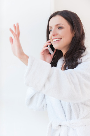 Hey darling! Beautiful young woman in bathrobe  talking on the mobile phone and smiling while looking through a window photo