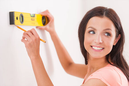 Handy around the home. Side view of cheerful young woman taking measurements of the wall and looking over shoulder photo