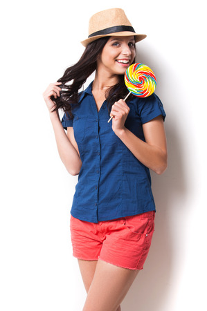 Sweet and extremely big. Young beautiful woman in funky hat holding a big lollipop and keeping mouth open while standing against white background photo
