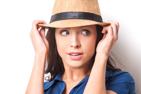 Confident and stylish beauty. Beautiful young woman in funky wear adjusting her hat and looking away photo