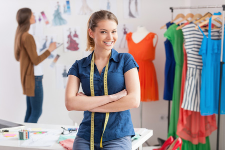 Fashion designers at work. Beautiful young woman with measuring tape on shoulders looking at camera and smiling while her colleague standing on background  photo