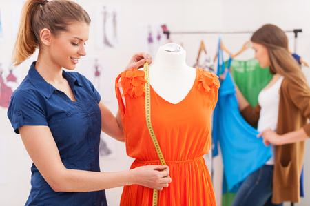 tailor measuring tape: Designer measuring dress. Beautiful female fashion designer measuring dress on the mannequin while her colleague standing on background Stock Photo