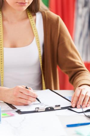 cropped: Fashion designer at work. Cropped image of female fashion designer sketching while sitting at her working place