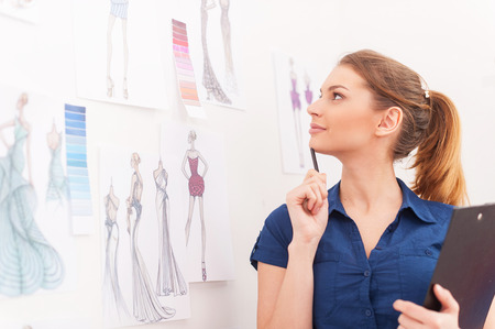 Creating a new fashion look. Beautiful female fashion designer holding clipboard and looking at the sketches hanging on the wall photo
