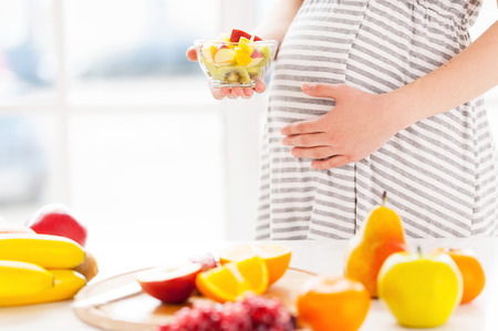 femme amoureuse: Seuls les aliments frais et sains pour mon b�b�. Image recadr�e de la femme enceinte tenant une salade de fruits plaque wirh