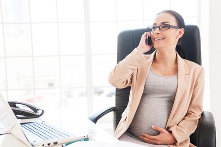 madre trabajadora: Se�ora del negocio embarazada en el trabajo. Alegre empresaria embarazada hablando por tel�fono mientras estaba sentado en su lugar de trabajo en la oficina