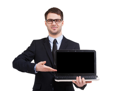 Presenting your product. Cheerful young man in formalwear pointing computer monitor and smiling while standing isolated on white photo