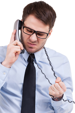 Fed up of office life. Furious young man in shirt and tie talking on telephone and expressing negativity while standing isolated on white Stock Photo
