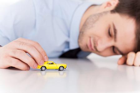 Dromen van een sportwagen. Vrolijke jonge man in overhemd en stropdas te spelen met speelgoed auto zittend op zijn werkplek Stockfoto